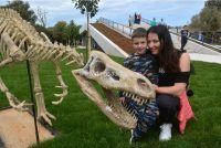 a kids and his motherm playing with dinosaurs